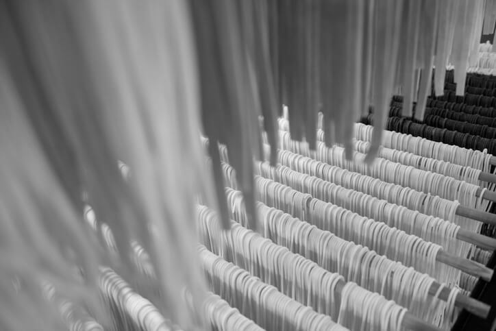 A black and white photo of long spaghetti strands hanging to dry